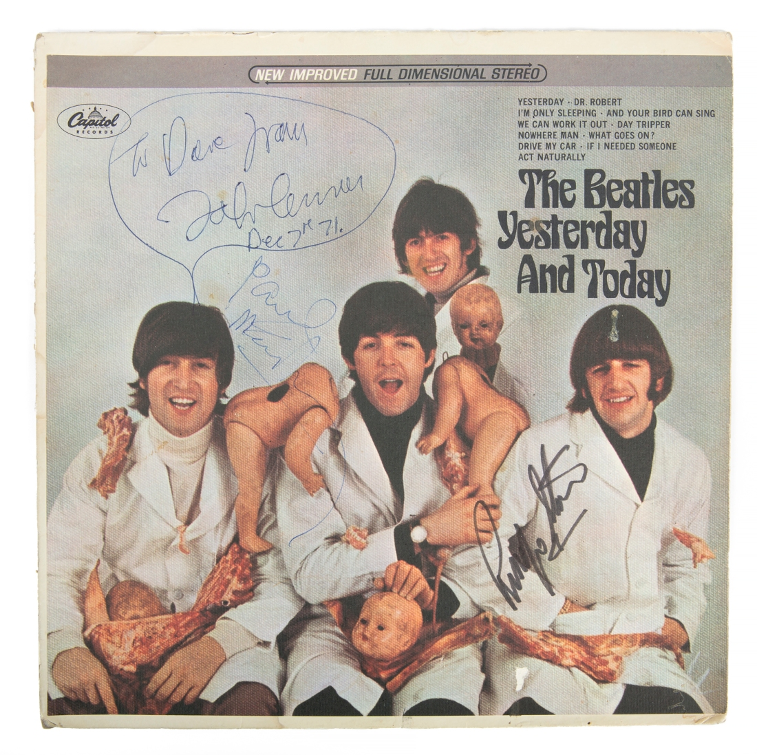 """John Lennon drew a speech bubble for the inscription on his copy of the infamous Beatles """"Butcher cover"""". The image shows McCartney, Lennon, Harrison, and Starr in white lab coats and draped with dismembered dolls and raw meat. McCartney signed it below Lennon's speech bubble. Starr signed the area over his right shoulder."""