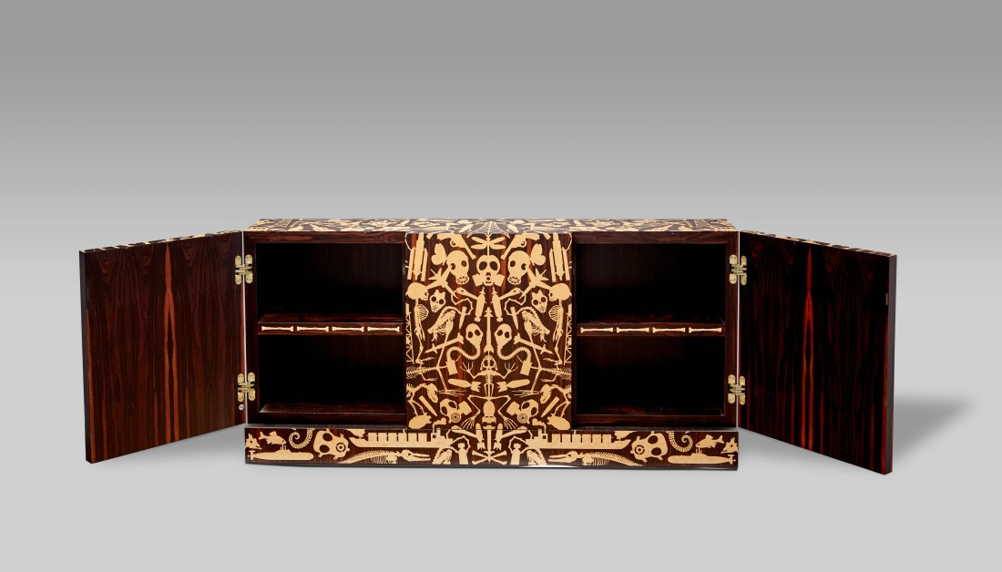 "A full shot of the unique ""dressoir"" made by Studio Job, with the doors open to reveal details of bird's eye maple bone images inlaid on the edges of the shelves."