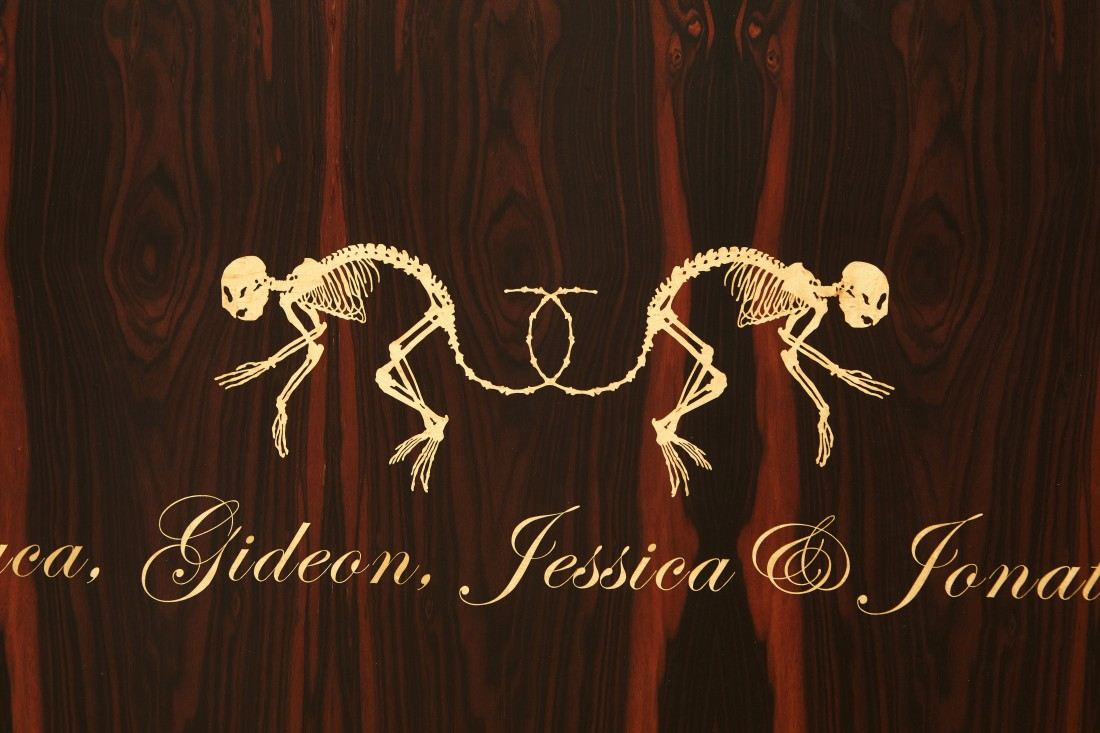 "Detail shot of the unique ""dressoir"" made by Studio Job in 2006, showing two primate skeletons with twined tails above the first names of the family members for whom it was commissioned."